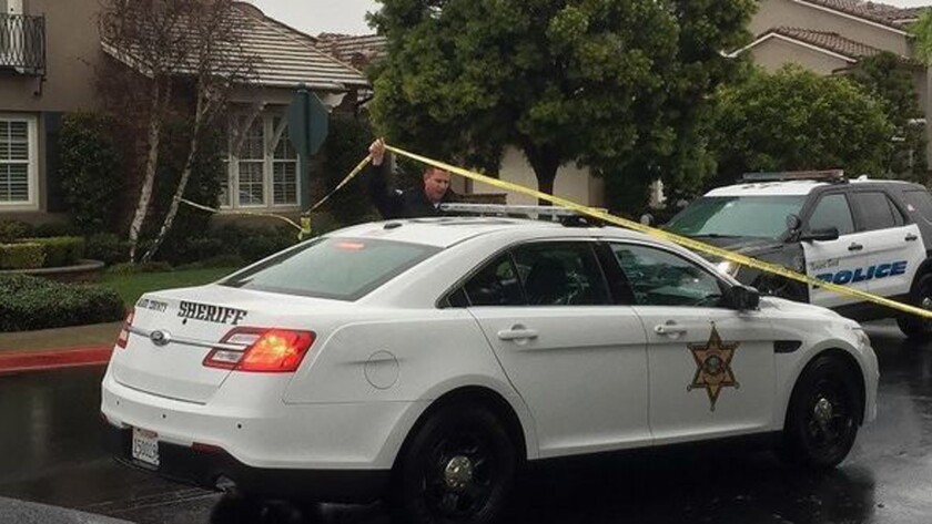 Authorities gather Thursday morning at the homicide scene on Palazzo in Bonita Canyon.