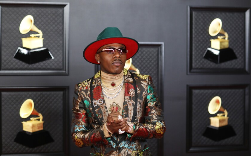 A man posing with his hands clasped in a green hat and patterned suit, surrounded by pictures of Grammy Awards.