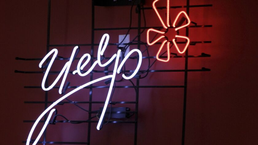 FILE - This Oct. 26, 2011, file photo shows the logo of the online reviews website Yelp in neon on a