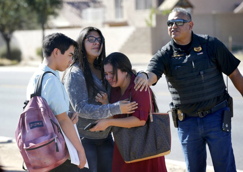 Students embrace after leaving campus, Friday, Feb. 12, 2016, in Glendale, Ariz. after two teens were shot Friday at Independence High School in the Phoenix suburb.   Two 15-year-old girls were shot once at the school, but it was not clear what led up to their deaths, Glendale Officer Tracey Breede
