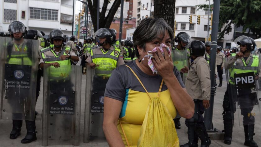 A woman protects herself from tear gas during protest in Caracas, Venezuela, on Friday. Several protests broke out after a Supreme Court ruling took power from congress raising fear of a dictatorship.