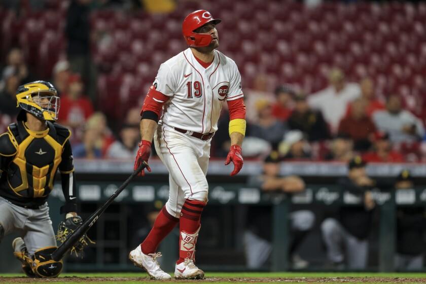 El jugador de los Rojos de Cincinnati Joey Votto (con el 19) mira su jonrón solitario en el quinto inning de su juego de béisbol contra los Piratas de Pittsburgh, en Cincinnati, el lunes 20 de septiembre de 2021. (AP Foto/Aaron Doster)
