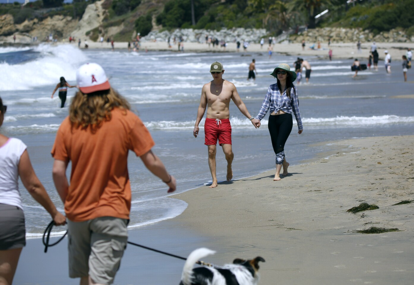 Dermatologists Dr. Anthony Huynh, center left, and Dr. Diana Zhang, both 47 and from Laguna Beach, enjoy a walk on the beach on a warm sunny day in Laguna Beach on Saturday.
