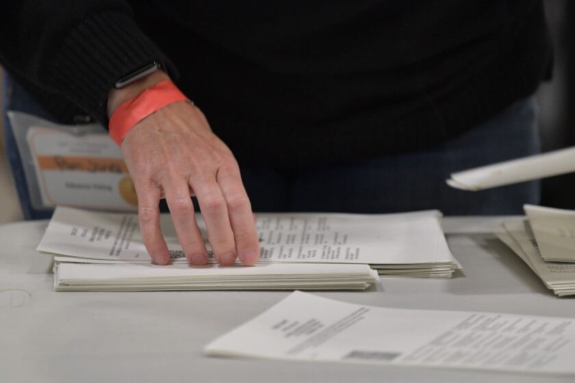 Cobb County election officials handle ballots during an audit in Marietta, Ga.