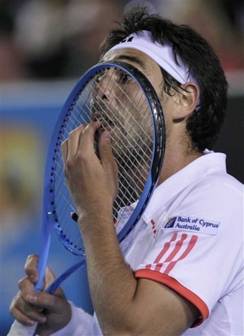Marcos Baghdatis of Cyprus sticks a finger through a racket as he plays Stanislas Wawrinka of Switzerland during their second round match at the Australian Open tennis championship, in Melbourne, Australia, Wednesday, Jan. 18, 2012. (AP Photo/John Donegan)