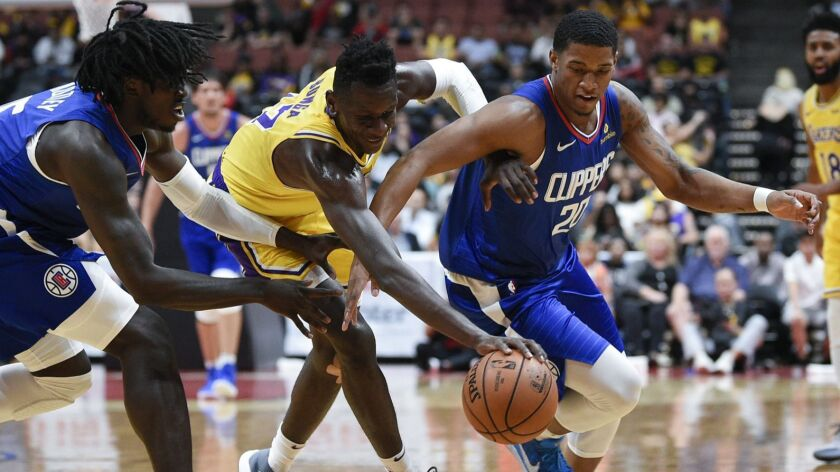 Desi Rodriguez, right, and Clippers teammate Johnathan Motley chase after a loose ball along with Lakers forward Isaac Bonga during a preseason game Saturday.