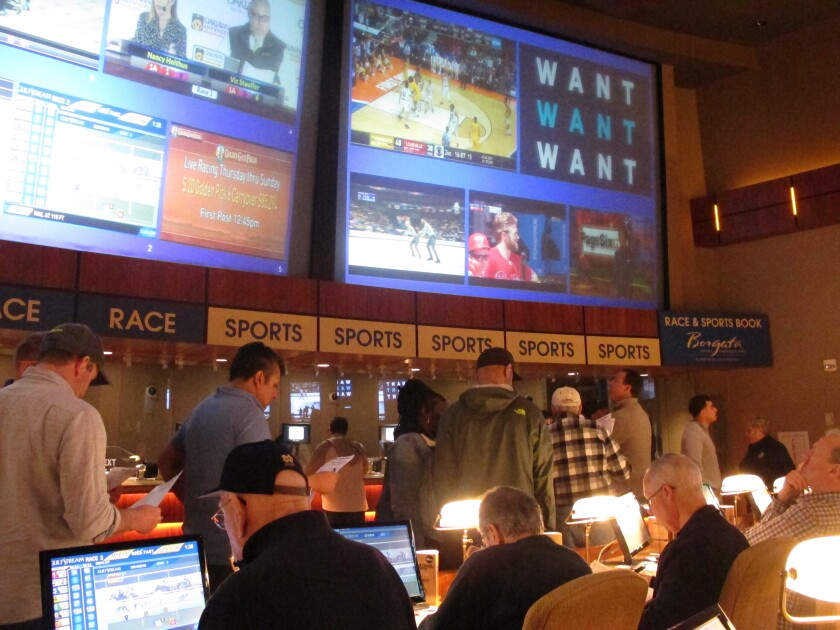 FILE - In this March 21, 2019 file photo, gamblers line up to place bets on the NCAA men's basketball tournament at the Borgata casino in Atlantic City N.J. After being closed since March due to the coronavirus outbreak, the Borgata will reopen to the general public on July 6, 2020, four days after much of its competition. Instead, the casino will be doing a test run for an invitation-only audience during those four days. (AP Photo/Wayne Parry, File)