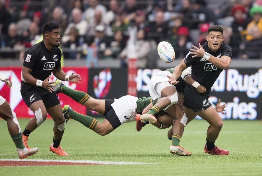 New Zealand's Tone Ng Shiu, right, passes to Vilimoni Koroi left, while being tackled by South Africa's Angelo Davids, front right, and Werner Kok during a semifinal match at the Canada Sevens rugby tournament in Vancouver, British Columbia, Sunday, March 8, 2020. (Darryl Dyck/The Canadian Press via AP)