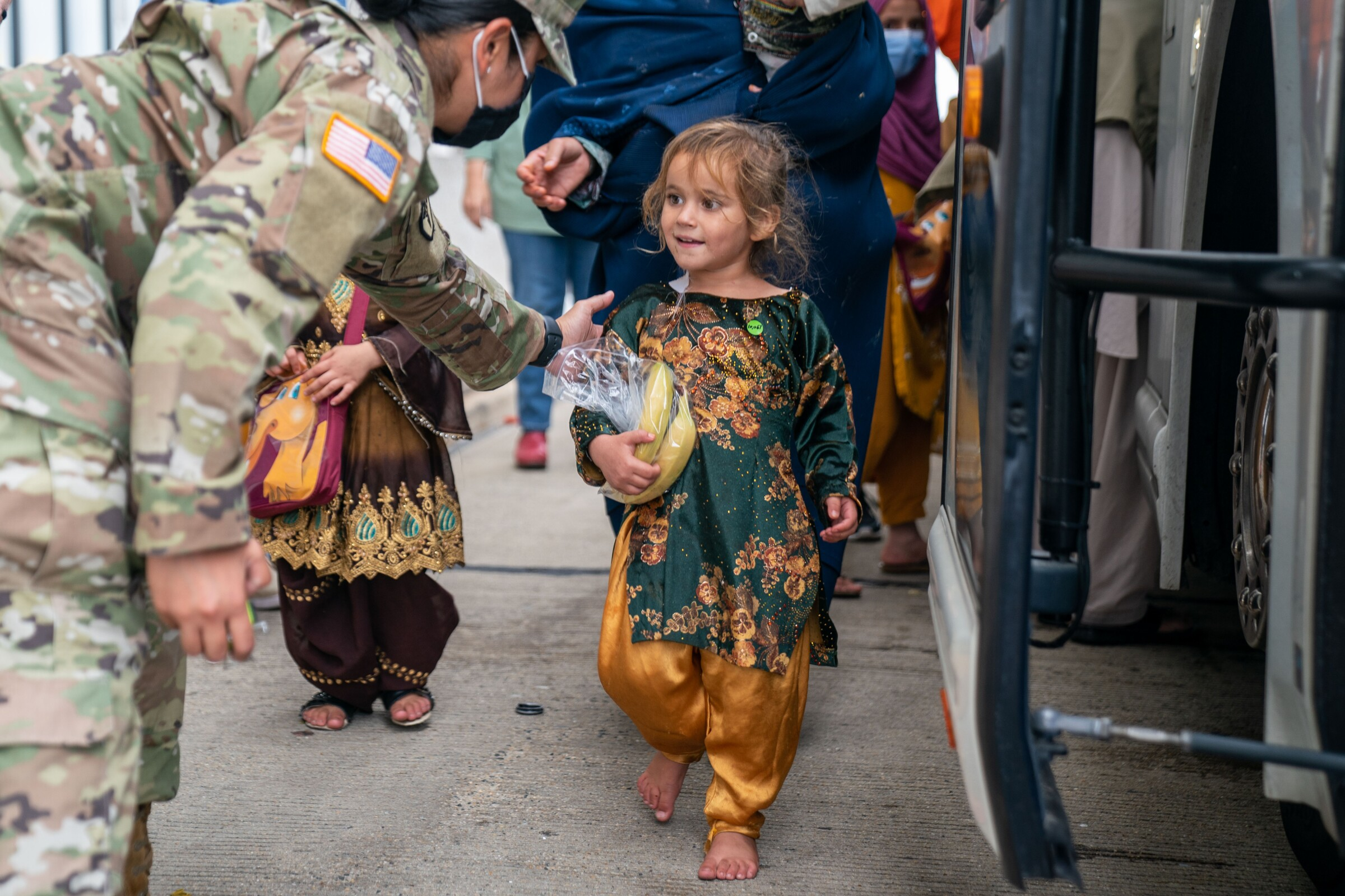 A U.S. service member greets a smiling child in a colorful outfit