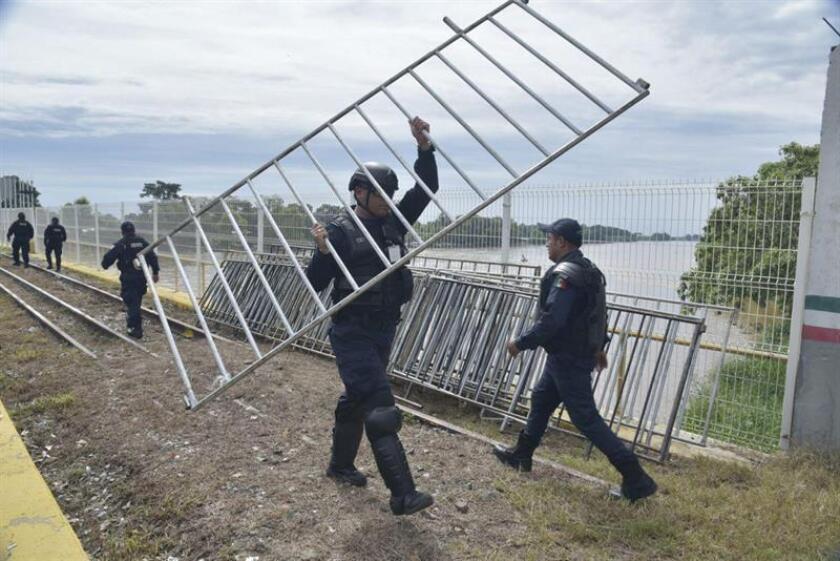 Policías federales de México colocan vallas metálicas para intentar contener a los miles de migrantes hondureños que ingresan por la frontera con Guatemala hoy, viernes 19 de octubre de 2018, en el margen del Río Suchiate (México). EFE