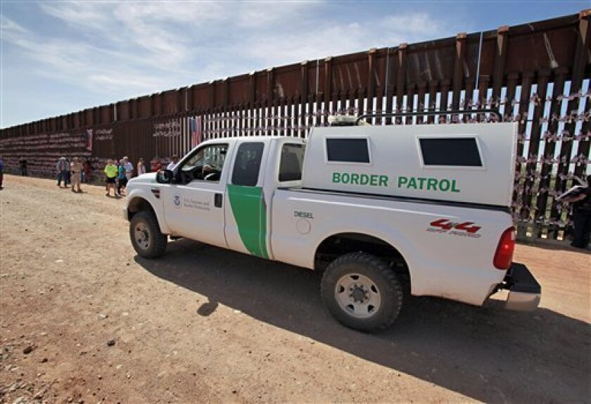 A U.S. Customs and Border Patrol agent patrols along the Arizona-Mexico border wall Sunday, Aug. 15, 2010 in Hereford, Ariz. as participants of the United Border Coalition Tea Party Rally gather along a remote stretch of the Arizona-Mexico border about 70 miles (113 kilometers) west of Nogales.(AP