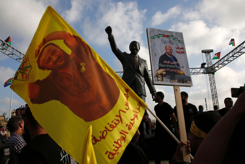 Protesters hold up portraits of Palestinian leader and prominent prisoner Marwan Barghouti in front of a statue of Nelson Mandela in the West Bank city of Ramallah this month.