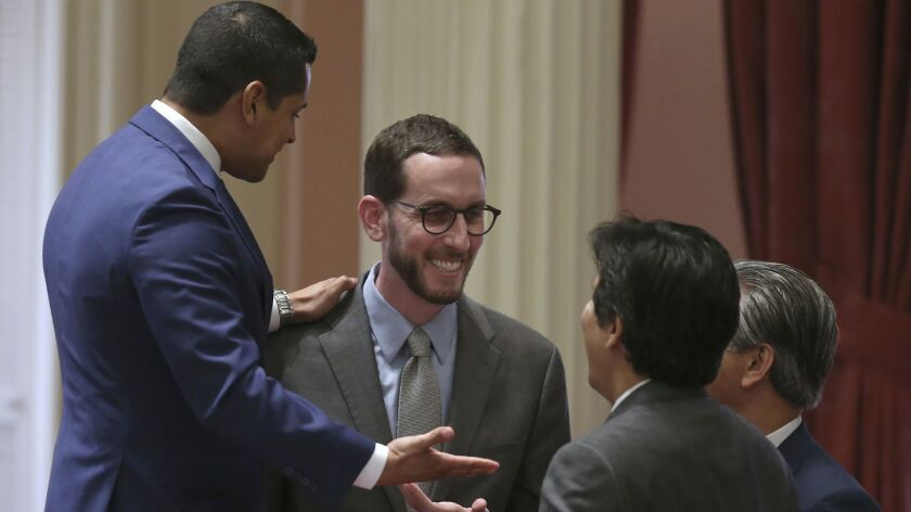 Assemblyman Miguel Santiago, D-Los Angeles, left, stands on a chair as he celebrates the passage of