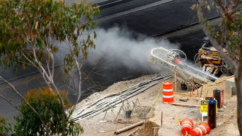 Natural gas spews out of a line that was ruptured at state Route 163 at Friars Road Wednesday, March 7, 2018, in Mission Valley.