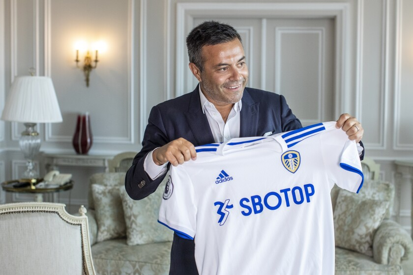 In this photo taken on Wednesday, Aug. 19, 2020, Leeds owner Andrea Radrizzani holds a Leeds shirt, during an interview with the Associated Press in Lisbon, Portugal. Leeds is counting on Marcelo Bielsa leading the team in the Premier League while planning for a future without the enigmatic manager. In his second season in charge, the Argentine ended the team's 16-year exile from the world's richest league by gaining promotion as Championship winners before his contract expired last month. (AP Photo/Manu Fernandez)