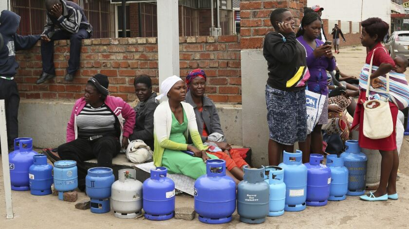 People wait in line for cooking gas at a garage in the Zimbabwean capital of Harare on Wednesday, Jan. 23, 2019.