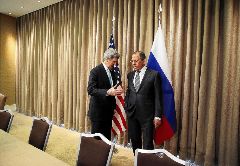 Secretary of State John F. Kerry, left, talks with Russian Foreign Minister Sergei Lavrov at the beginning of a meeting on the Ukraine crisis in Geneva.