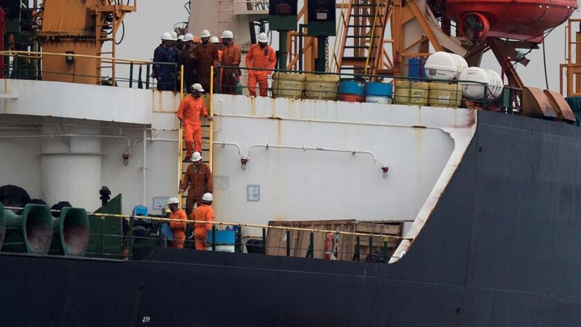 Crew members walk down a ladder on Grace 1, an Iranian tanker seized by Gibraltar.