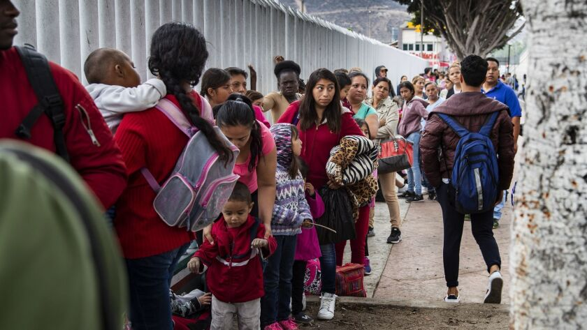 Asylum-seeking immigrants line up at a border fence in Tijuana, Mexico.