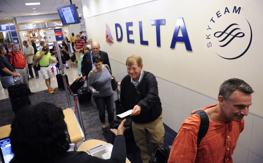 Delta passengers board their flight at Hartsfield-Jackson Atlanta International Airport in Atlanta in a 2013 file photo. The world's busiest airport's wi-fi is back up and running after a cyberattack that hit the city last month.