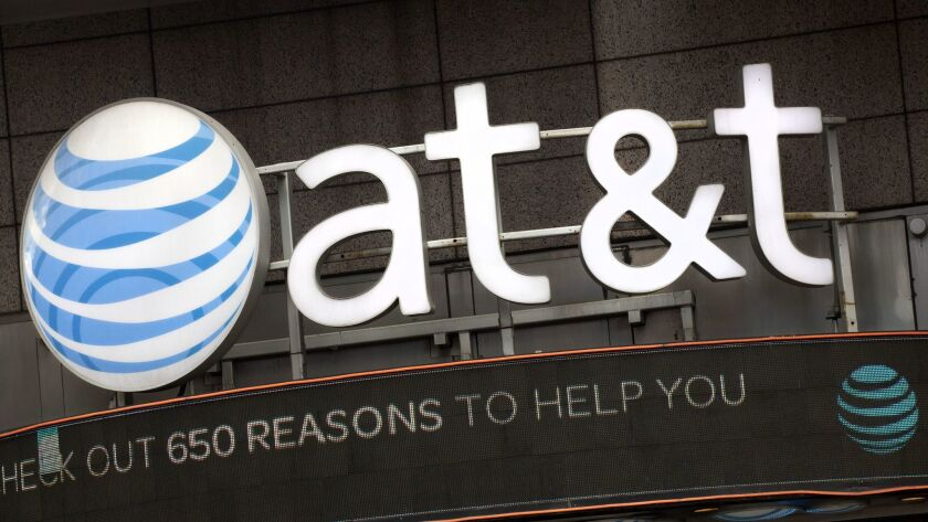 FILE - In this Monday, Oct. 24, 2016, file photo, the AT&T logo is positioned above one of its retai