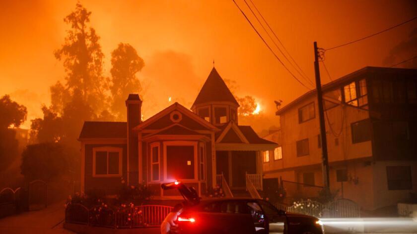 Una familia evacúa mientras el fuego se acerca a su casa, en Ventura, el martes pasado (Marcus Yam / Los Angeles Times).