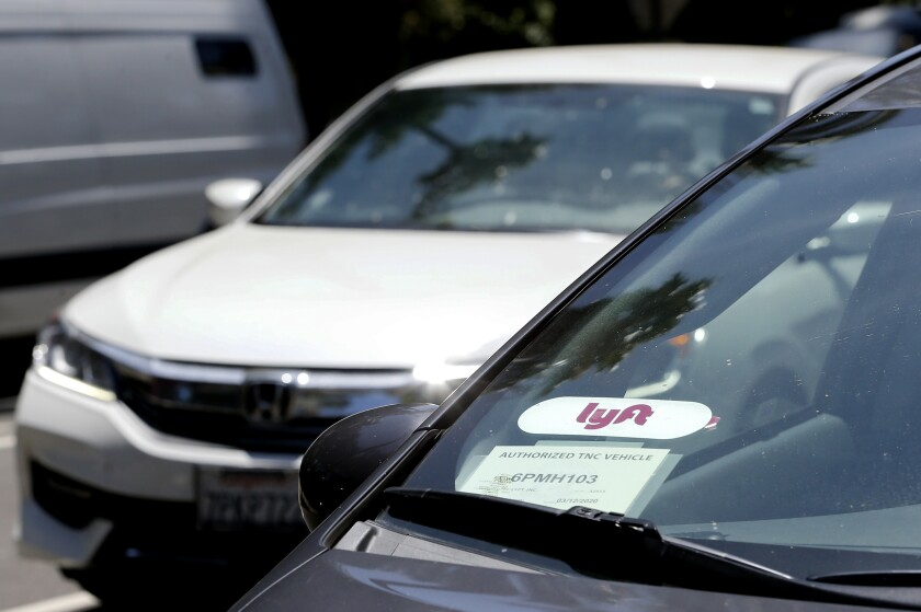 In this file photo a Lyft ride-share car waits at a stoplight in Sacramento, Calif.