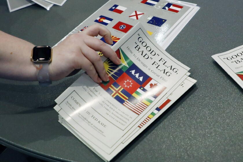 "A member of the state Department of Archives and History prepares a handout of materials on how to design a flag for members, following the first meeting of the Flag Commission, Wednesday, July 22, 2020, in Jackson, Miss. The group has the duty to design a new Mississippi flag without the Confederate battle emblem and the banner must include the phrase, ""In God We Trust."" (AP Photo/Rogelio V. Solis)"
