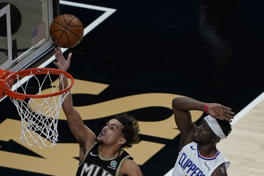 Atlanta Hawks guard Trae Young goes up for a basket as Clippers guard Reggie Jackson defends.