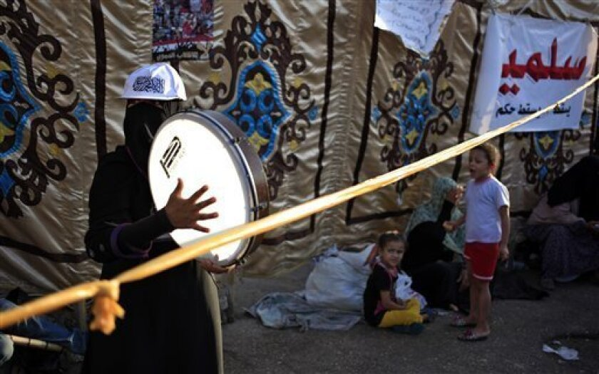 """A Supporter of Egypt's ousted President Mohammed Morsi plays drum during a protest outside Rabaah al-Adawiya mosque, where protesters have installed a camp and hold daily rallies at Nasr City in Cairo, Egypt, Thursday, Aug. 1, 2013. Arabic writing on the banner on the right side reads, """"Peaceful."""" (AP Photo/Khalil Hamra)"""