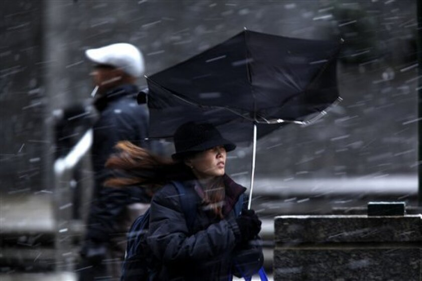 FILE - In this Feb. 25, 2010 file photo, a woman's umbrella is upset from a gust of wind during a winter snow storm in Philadelphia. Snowstorms that shut in shoppers last month also chilled sales at women's clothing stores compared with a year earlier, but most retail sectors saw gains in February, data released Wednesday show. (AP Photo/Matt Rourke, file)
