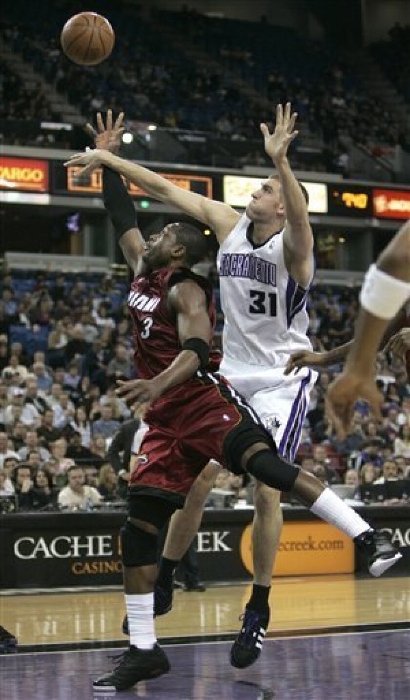 Miami Heat guard Dwyane Wade shoots as Sacramento Kings center Spencer Hawes, right, defends during the first quarter of an NBA basketball game in Sacramento,  Calif., Friday, Jan. 9, 2009. (AP Photo/Rich Pedroncelli)