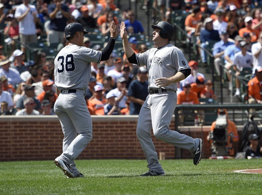 New York Yankees' Rob Refsnyder (38) high-fives Chase Headley, right, after they scored on a single by Austin Romine during the first inning of a baseball game against the Baltimore Orioles, Sunday, Sept. 4, 2016, in Baltimore. (AP Photo/Nick Wass)
