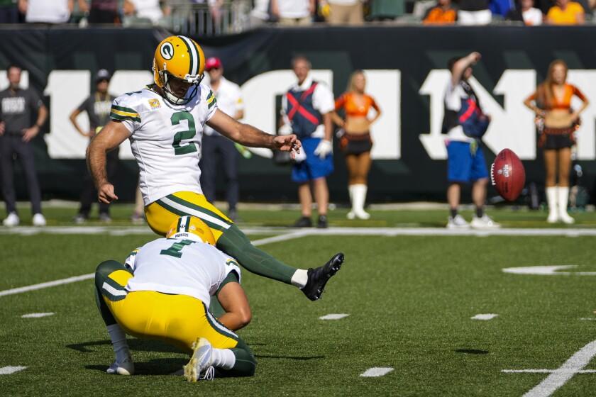 Green Bay Packers kicker Mason Crosby (2) kicks a field goal from he hold of Corey Bojorquez in the second half of an NFL football game against the Cincinnati Bengals in Cincinnati, Sunday, Oct. 10, 2021. (AP Photo/AJ Mast)