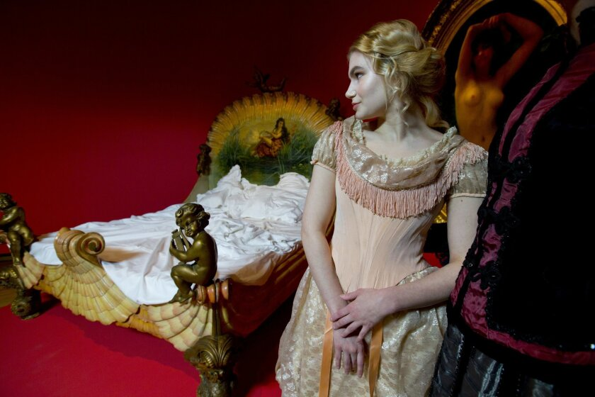 Models pose next to a 19th century bed of a French courtesan during a photo call for the upcoming exhibit Easy Virtue at the Van Gogh Museum in Amsterdam, Netherlands, Tuesday, Feb. 16, 2016. The exhibit, which runs from Feb. 19 till June 19 2016, shows prostitution through the eyes of Vincent van