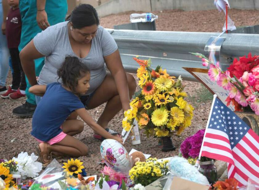 A family places flowers at a memorial outside the Cielo Vista Mall Walmart in El Paso, where 20 people were shot and killed by a gunman in August. The store is set to reopen Nov. 14.