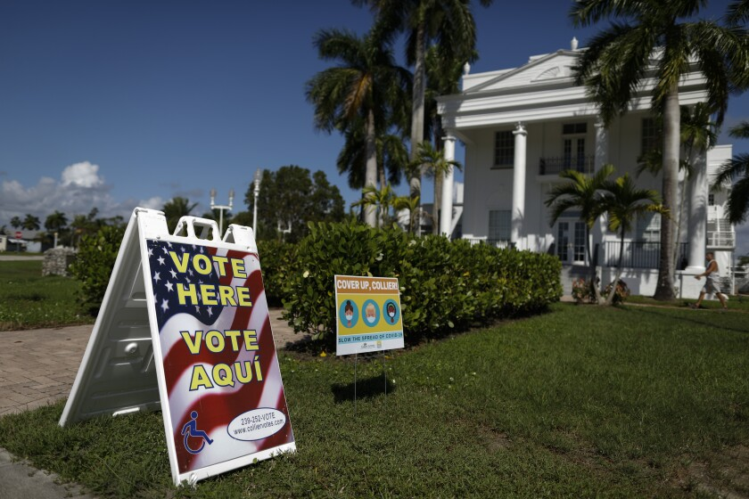 """A man walks into City Hall, with a """"Vote Here"""" outside, in Everglades City, Fla."""