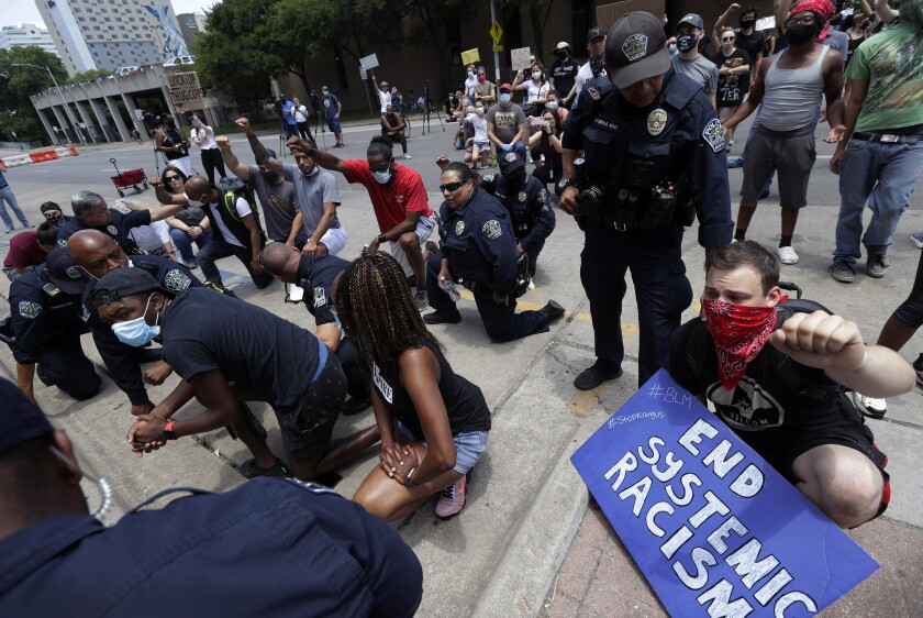 Members of the Austin Police Department in Texas kneel with demonstrators June 6 protesting the death of George Floyd.