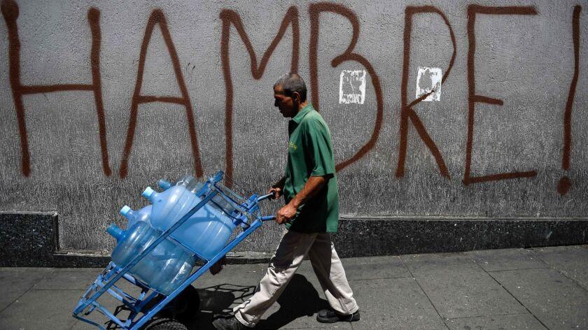 "A man pushes a cart past graffiti reading ""Hunger"" in Caracas, Venezuela."