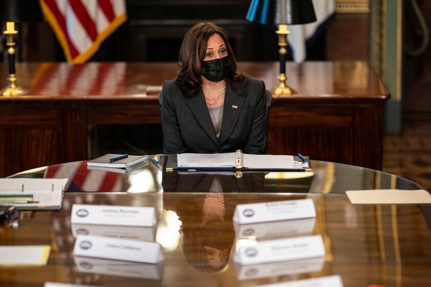 Vice President Kamala Harris wears a face mask sitting at a big table.
