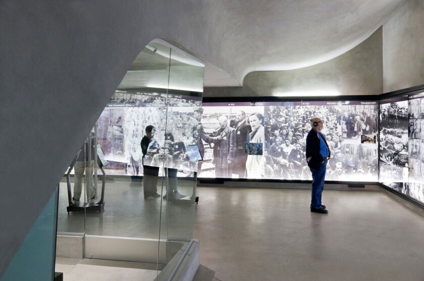 People looking at exhibits at the Los Angeles Museum of the Holocaust, now renaming itself Holocaust Museum Los Angeles.