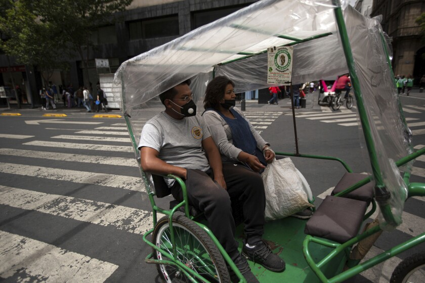 Shoppers wearing protective masks to curb the spread of the new coronavirus, ride in a bicycle taxi in downtown in Mexico City, Thursday, Aug. 13, 2020. With the country facing a deep economic recession, Mexican President Andres Manuel Lopez Obrador has pushed to reopen the economy quickly even as COVID-19 infections and deaths continue to rise. (AP Photo/Fernando Llano)