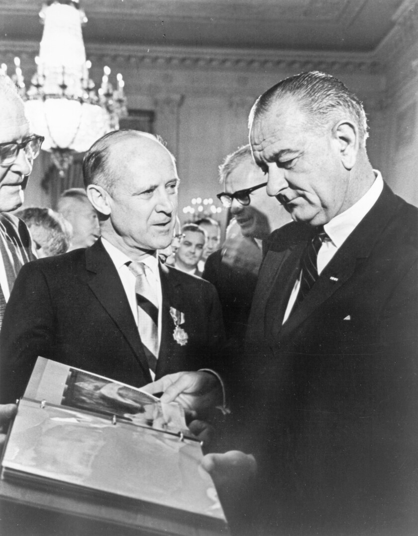 Dr. William H. Pickering (left), Directory of the Jet Propulsion Laboratory, presents Mariner spacecraft photos to President Lyndon Baines Johnson in 1964