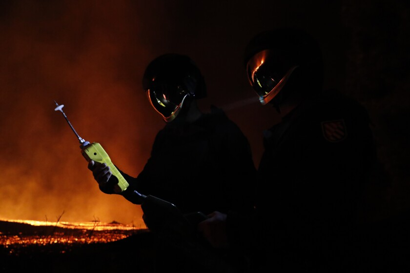 Personnel illuminated from behind by a volcanor take gas reading measurements on the Canary island of La Palma, Spain.