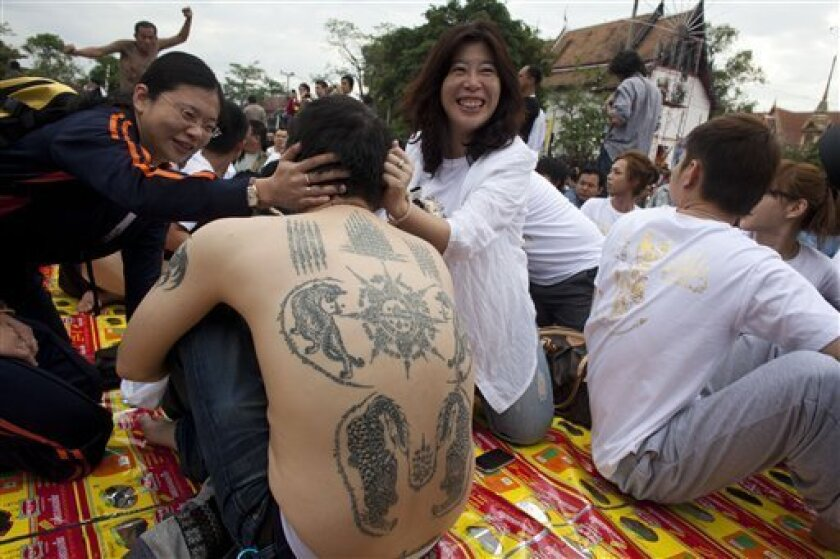 """In this March 19, 2011 photo, a foreign tourist has his tattoos admired during a tattoo festival at Wat Bang Pra in Nakhon Chaisi, Thailand. Thailand's Culture Minister Niphit Intharasombat has announced that foreign tourist should be banned from getting religious tattoos while visiting Thailand, saying the practice is culturally insensitive. """"Foreigners see these tattoos as a fashion,"""" Niphit said in the statement posted on his ministry's website Thursday, June 2, 2011. """"They do not think of respecting religion, or they may not be aware"""" that it can be offensive. As of yet the practice is still not illegal under Thai law. (AP Photo/David Longstreath)"""