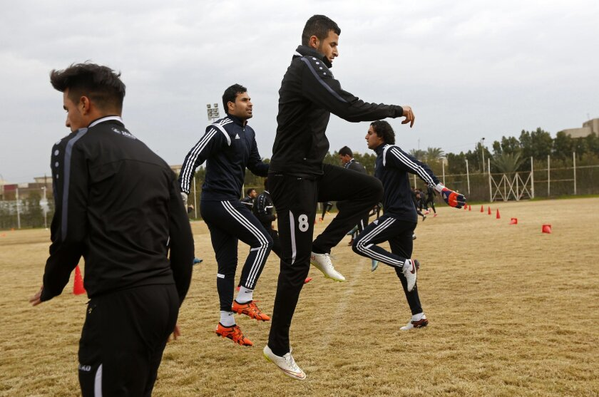 In this Saturday, Feb. 6, 2016 photo, Soccer player Ayman Hussein, center, trains with his team in Baghdad, Iraq. Islamic State militants drove Hussein from his home. Eighteen months later, he sent Iraq's soccer team to the Olympics. Hussein kicked the game-winning goal against Qatar last month in