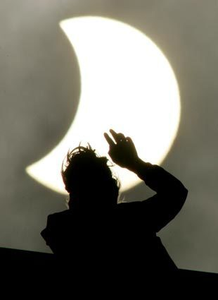 A woman looks at a partial solar eclipse in St. Petersburg, Russia.