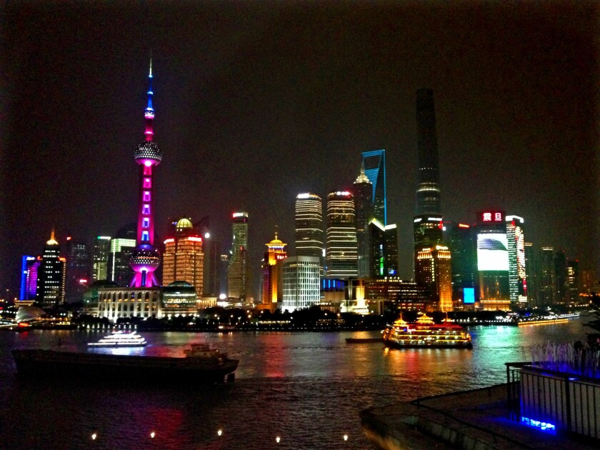 High-rise buildings in central Shanghai lighted up at night.