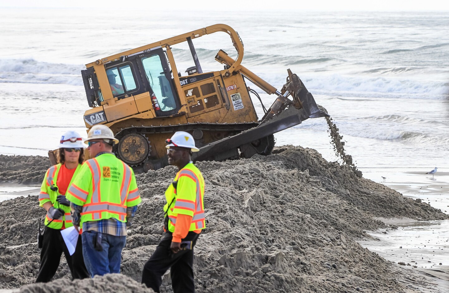 Crews build a training dike that will help direct sand replenishment at Cardiff State Beach.