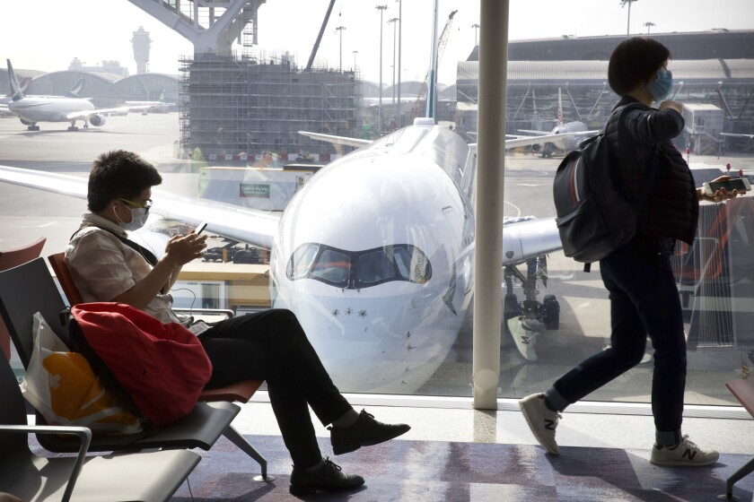 Travelers wear masks as they wait for their flights at Hong Kong International Airport on Jan. 21. The outbreak could affect global travel and tourism industries if it is not contained quickly, expert say.